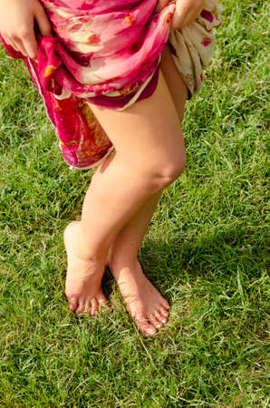 High angle view of a pair of sexy shapely barefoot female legs posing on green grass