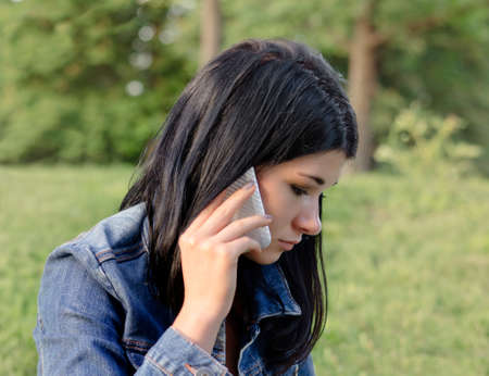 Beautiful young girl listening to a call on her mobile with a serious concerned expression as she stands outdoors in a denim jacket in a park