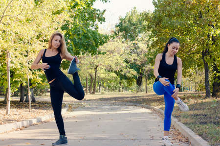 Two friends exercising together in a park doing stretching exercises to limber up their muscles before doing a training workout photo