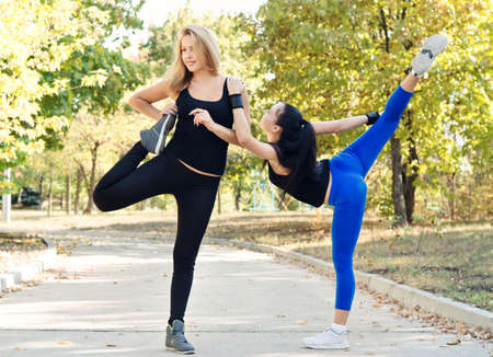 limbering: Two friends exercising together in a park doing stretching exercises to limber up their muscles before doing a training workout