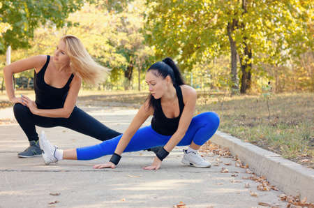 limbering: Two fit athletic young woman working out together on a road in a park doing stretching exercise and leg extensions to improve suppleness and mobility Stock Photo