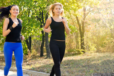Two attractive young female friends jogging together in a park doing an early morning training workout photo
