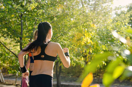 Fit athletic young woman jogging through a sunny park between leafy green trees as she does her daily workout photo