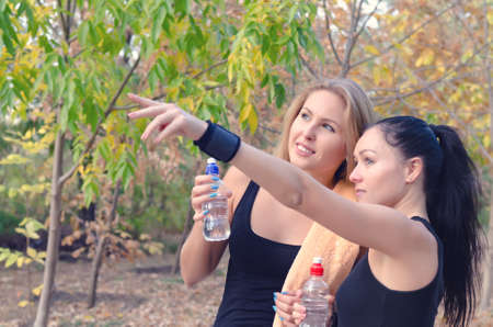 Two fit young women athletes drinking bottled water as they take a break from their training workout as one points to something in the distance photo
