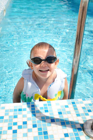 pool preteen: Laughing little boy climbing out of a swimming pool on the aluminium stepladder wearing goggles and a flotation grinning happily at the camera jacket