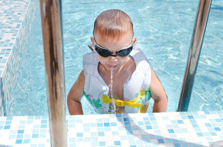 flotation: Little boy spitting out a mouthful of water as he hangs onto the steps at the side of a swimming pool in his goggles and flotation jacket