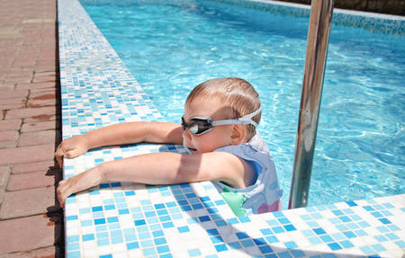 buoyancy: Small boy clambering out of a swimming pool onto the mosaic surround goggles and buoyancy jacket