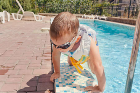 Small boy clambering out of a swimming pool onto the mosaic surround in his goggles and buoyancy jacket