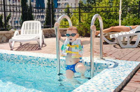 buoyancy: Small boy clambering out of a swimming pool onto the mosaic surround in his goggles and buoyancy jacket