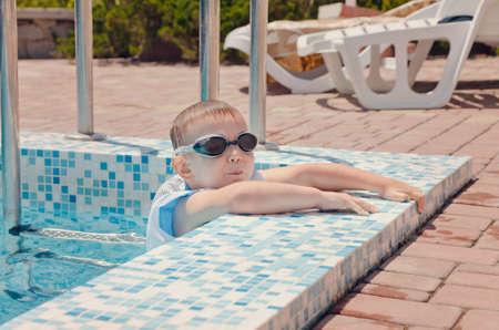 buoyancy: Peque�o ni�o trepando fuera de una piscina en la envolvente de mosaico en las gafas y chaqueta de flotaci�n
