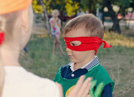 preteen boys: Young boy playing at a kids birthday party wearing a super hero mask as he chats to his young friends
