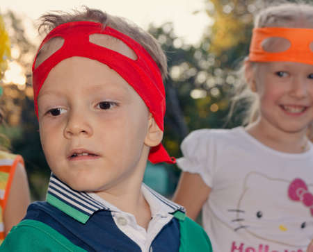 Handsome young boy at a childs birthday party wearing a super hero mask pushed up on his forehead as he watches something to the left of the frame photo