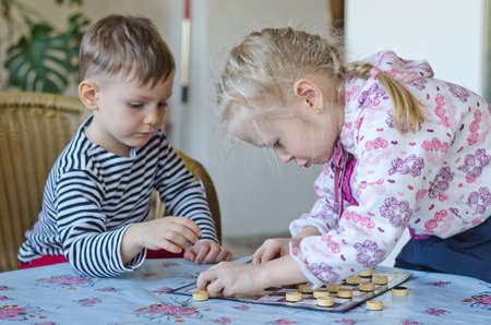 draughts: Young girl and boy playing checkers or draughts together with the little girl bending over the board moving her counters watched closely by her brother