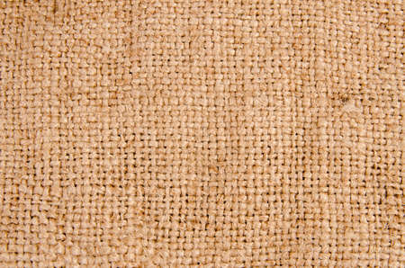 gunny: Background texture of burlap or hessian cloth showing the weave detail and natural fibres with corner vignetting