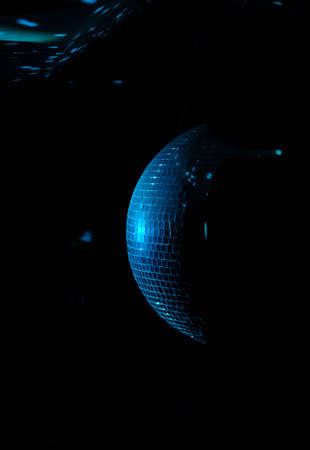 mirrored: Colorful turquoise blue mirrored metallic disco ball in a nightclub hanging in the darkness with copyspace