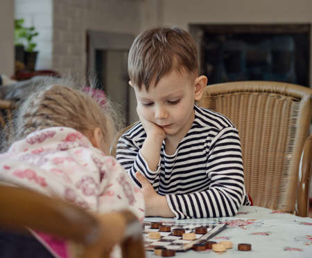 he   my sister: Little boy planning his strategy staring thoughtfully at the board as he sits at a table playing a game of checkers or draughts with his sister