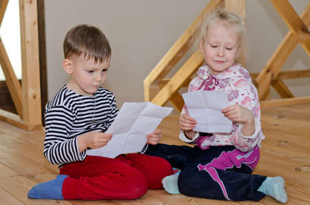 Little boy and girl sitting together on a wooden floor each reading a letter or note on a sheet of paper with serious engrossed expressions Stock Photo