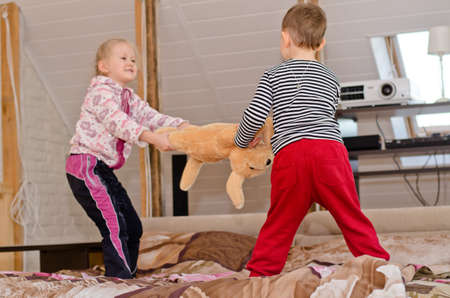 Cute little brother and sister having a playful tug of war as they stand up on a bed laughing and smiling and pulling in opposite directions on a large stuffed toy dog photo