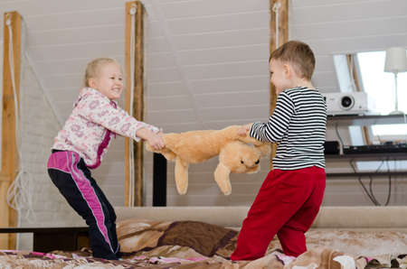 possessive: Cute little brother and sister having a playful tug of war as they stand up on a bed laughing and smiling and pulling in opposite directions on a large stuffed toy dog