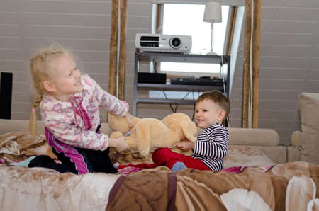 Cute little brother and sister having a playful tug of war as they stand up on a bed laughing and smiling and pulling in opposite directions on a large stuffed toy dog