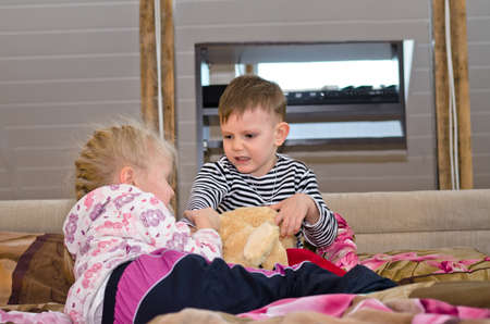 tugging: Brother and sister having a tug of war as they lie together on a bed pulling in opposite directions on a large soft stuffed toy dog Stock Photo