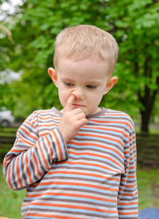 nose picking: Candid image of a thoughtful little boy standing picking his nose outdoors in a garden or park Stock Photo