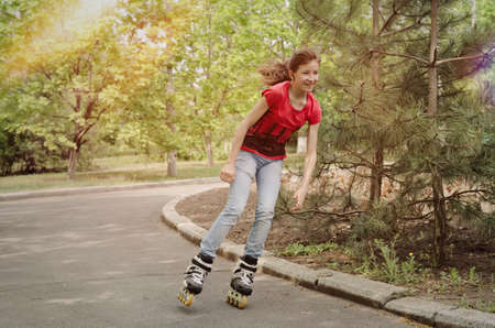 cornering: Beautiful young teenage girl roller skating cornering at speed on a tarred rural road with her ponytail flying out behind her