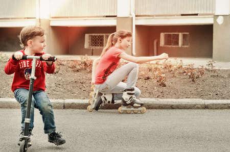 Kleine jongen rijdt een stuk speelgoed scooter op een geasfalteerde weg op zoek naar een jonge tiener meisje op rolschaatsen kijken