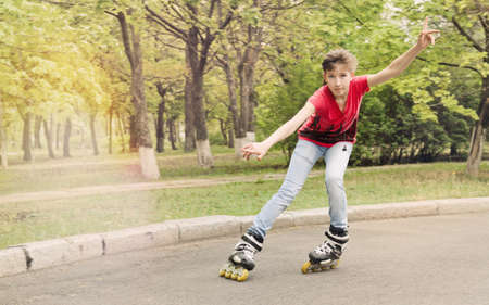 roller skating: Attractive teenage girl roller skating on roller blades on a tarred rural road rounding a bend at speed with her arms flying Stock Photo