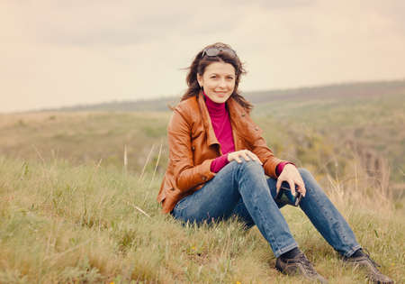 Beautiful trendy young woman outdoors sitting on a grassy hill photo