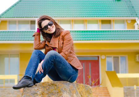 Beautiful charming stylish young woman in a trendy leather jacket with her sunglasses balanced on top of her head sitting smiling confidently at the camera in front of a house photo