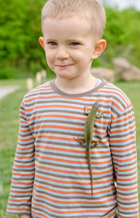 unafraid: Cute little boy with a live green lizard clinging to his chest on his shirt giving the camera an amused whimsical smile Stock Photo