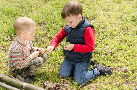 Two small boys lighting a fire in woodland setting fire to a pile of leaves and twigs in the grass as they enjoy a day camping in nature