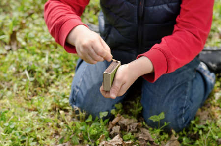 Young boy lighting a fire outdoors kneeling down in the grass striking a match against the box photo