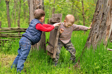 Two young boys fighting over a rustic old gate with one trying to keep it open as the second tries to close it as they enjoy a day out playing in the countryside Stock Photo