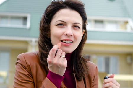 refreshes: Beautiful young woman applying lipstick to her lips outside a house as she refreshes her makeup during the day, close up of her face