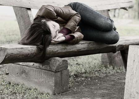 Zwart-wit beeld van een vrouw lag opgerold slapen op een rustieke houten bankje in het park, conceptuele van dakloosheid, uitputting en eenzaamheid