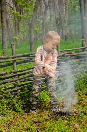 Little boy putting out a small camp fire in front of a rustic wooden fence with a beaker of water photo