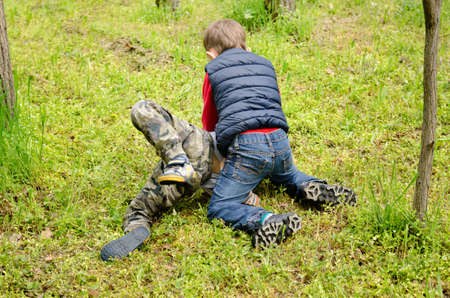 Two young boys fighting on the ground with one on top of the other holding him down on the grass photo