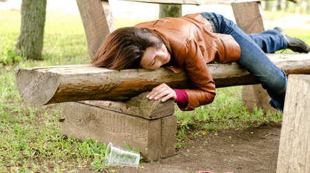 Drunk woman sleeping it off on a wooden bench in a park lying face down in her leather jacket fast asleep