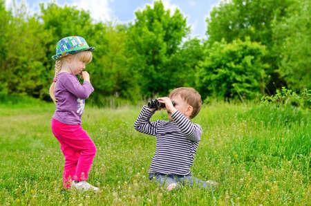 小さな女の子と男の子を探索し、学習の性質についての教育の日を楽しむ緑の草原に座っている双眼鏡で遊んで 写真素材
