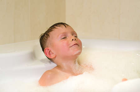 Little boy with eyes closed having a relaxing bubble bath photo