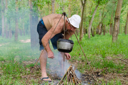 Shirtless man starting a cooking fire in a campsite lighting the pyramid of kindling as an iron cauldron swings from a frame above photo
