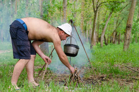 kindling: Man lighting a cooking fire while camping with a firelighter with iron pots on frames swinging overhead and cars visible parked in the woodland behind