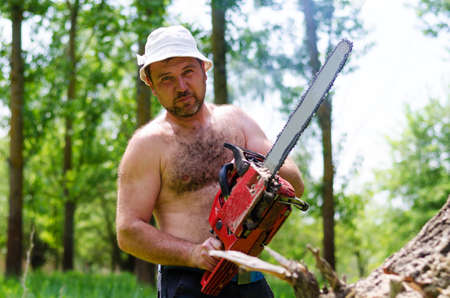 Fit shirtless man wearing a hat carrying a portable petrol chainsaw in woodland as he prepares to fell a tree for fuel photo