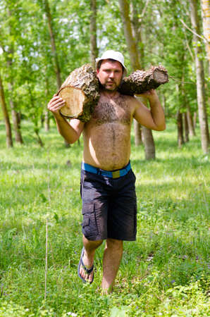 Shirtless strong muscular man carrying a large log of wood walking across in front of the camera as he fells wood for the camp fire photo