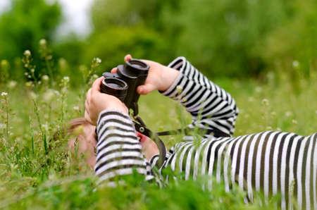 Niño pequeño que usa un par de binoculares para mirar hacia el cielo mientras yace boca arriba en una pradera rural cubierta de hierba disfrutando de un día en la naturaleza