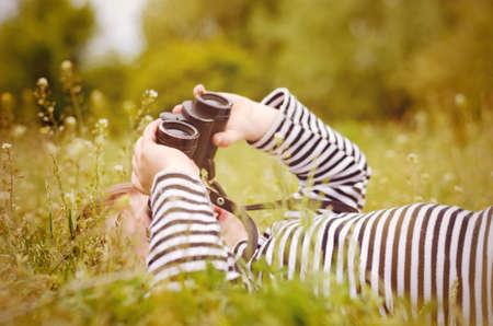 Jong kind met behulp van een verrekijker te kijken naar de hemel als hij ligt op terug in een grazige landelijke weide genieten van een dag in de natuur Stockfoto