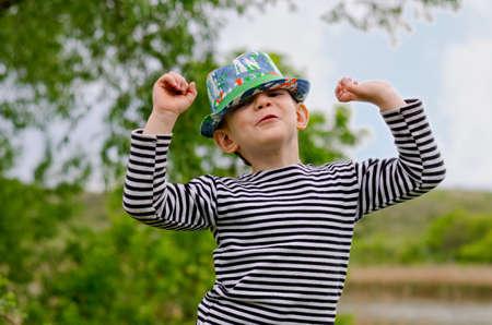 jaunty: Jaunty ni�o machista en un sombrero de moda de colores con una sonrisa maliciosa que levanta sus brazos en el aire mientras se exhibe en un parque de verano Foto de archivo