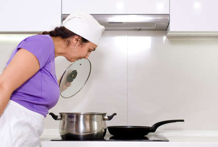 Female cook watching a pot boil on the stove in her white apron and chefs toque photo